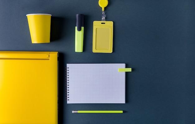 黒い背景にメモ帳、マーカー、バッジ、コンピューター、黄色い鉛筆が横たわっている