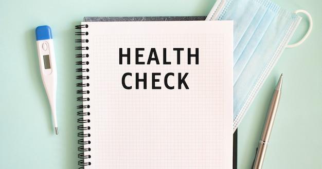青色の背景にメモ帳、医療用マスク、体温計、ペン。ノートブックのヘルスチェックテキスト。医療の概念。