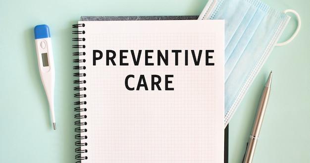 青色の背景にメモ帳、医療用マスク、体温計、ペン。ノートブックの予防ケアテキスト。医療の概念。