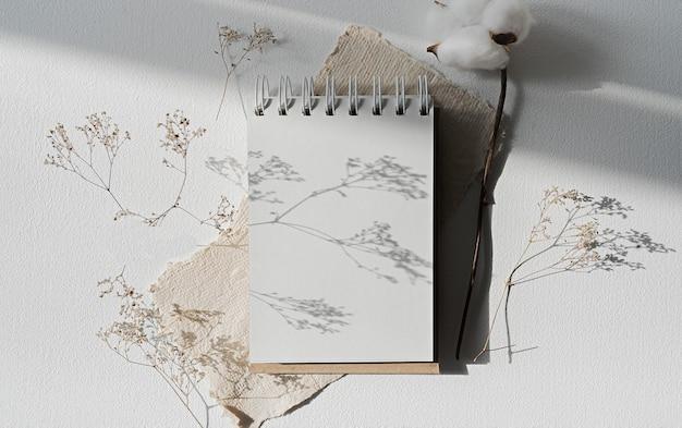 삽화와 디자인을 보여주는 메모장 모형. 빈 페이지가 열려 있는 노트북은 마른 식물로 둘러싸인 흰색 테이블에 놓여 있습니다. 스케치북이나 도화지를 최소한으로 조롱합니다.