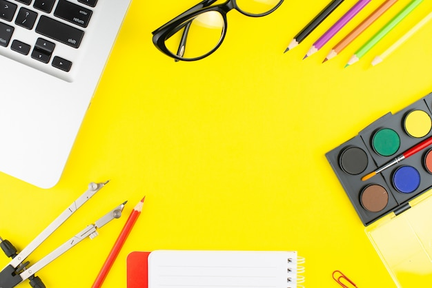 Notepad, multicolor pencils, divider, black glasses, colorful clips, colors for drawing and laptop