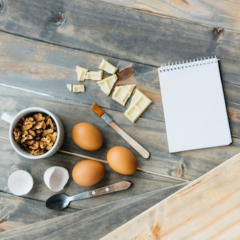 Notepad near chocolate pieces; eggs and walnuts on wooden surface