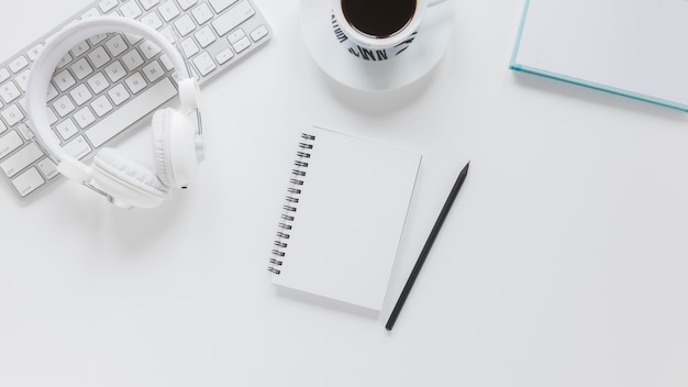 Notepad near electronic gadgets and coffee cup