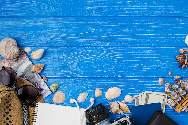 Notepad near hat with earphones and money among seashells and camera