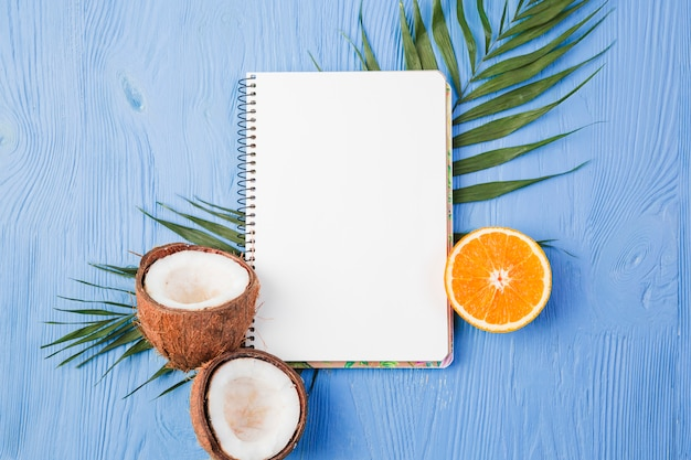 Notepad near plant leaves with fresh coconuts and orange on board