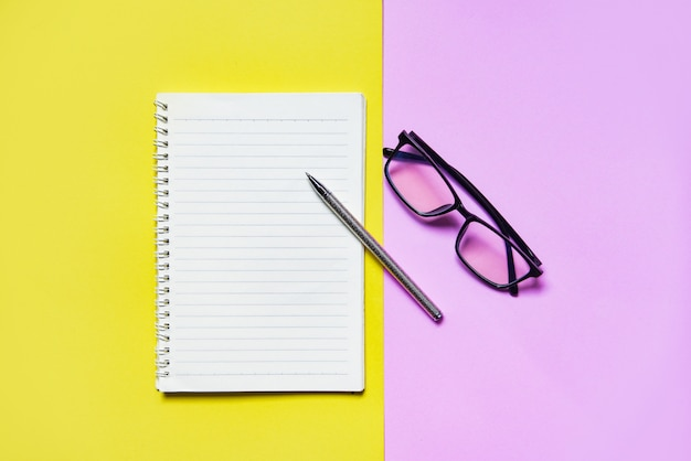 Notepad or notebook paper with pen and glasses on yellow pink for education and business concept