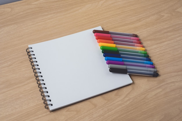 Notepad or notebook with many colorful pens on brown wood table