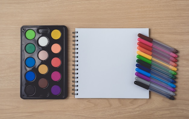 Notepad or notebook with many colorful pens and watercolor palette on brown wood table.using for arts and education