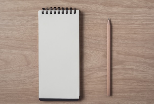 Notepad or notebook with pencil on brown wood table.using for education, business