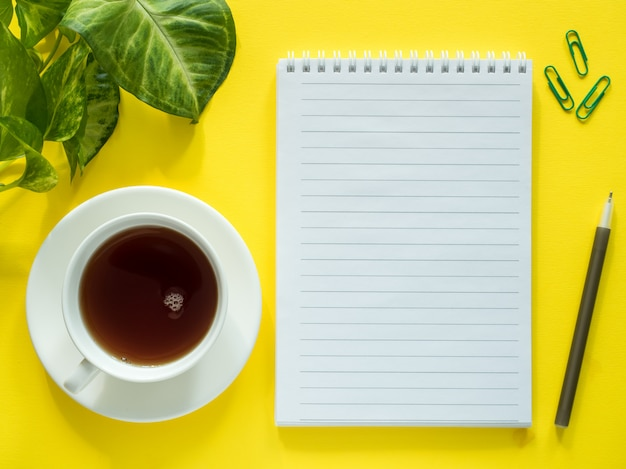 Notepad for notes, green leaves plant coffee cup on yellow desktop, flat lay, copy space.