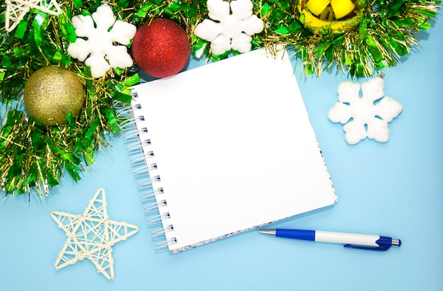 A notepad for notes with a pen and christmas decorations new years blue background