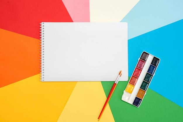 Блокнот на красочном фоне. канцелярские товары для рисования. вид сверху.