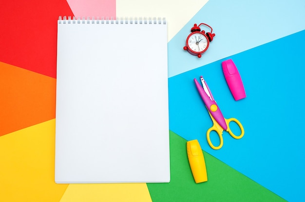 カラフルな背景のメモ帳。リストや計画を書く。描画、ビジネス、教育のための文房具。テキスト用のスペースをコピーします。上からの眺め。