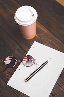 テーブルの上のメモ帳コーヒーカップペンフラワー鉢植えのオフィス文房具