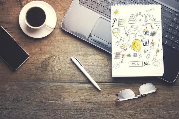 ノートパソコン、コーヒー、筆記具、木製テーブルのコーヒーの上のメモ帳