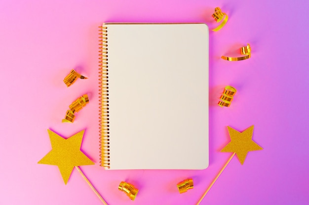 Блокнот с золотыми лентами и золотыми звездами на розовой поверхности