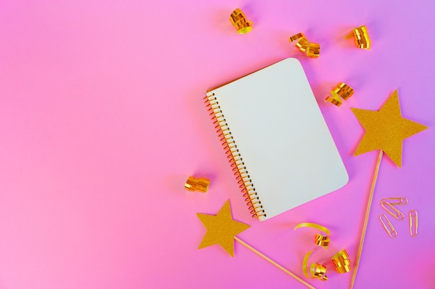 Notepad paper with golden ribbons and gold stars on pink background