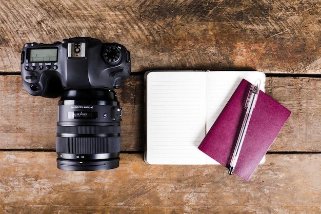 나무 배경에 메모장, 여권, 펜 및 dslr 카메라