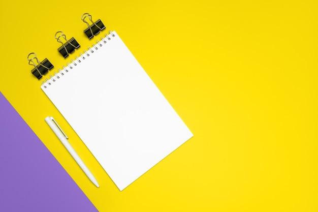 Блокнот, ручка и зажимы для папок на желтом фоне. плоская планировка, вид сверху, копия пространства.