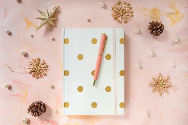 Ручка блокнота и новогоднее украшение на рабочем столе стола