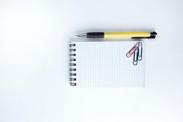 Блокнот ручка и скрепка на белом фоне фото с копией пространства