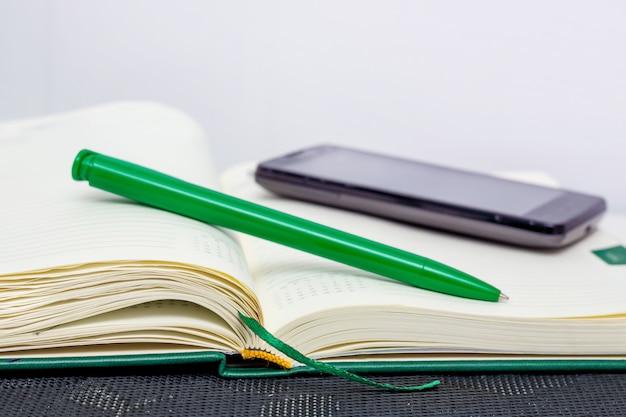 Блокнот, ручка и телефон крупным планом