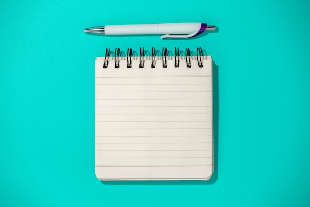 Notepad and pen on blue background, top view
