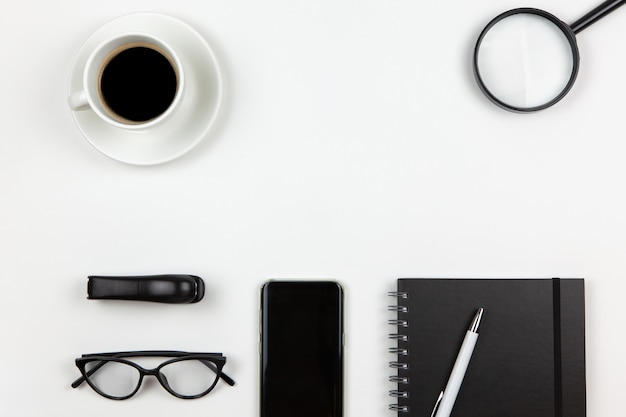Notepad, pen, coffee, smart phone, magnifier, glasses on white background, copy space, flat lay.