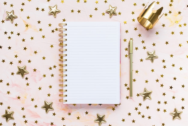 Notepad, pen, gold crown and stars decoration on woman desk workspace, pink background. winter holidays holidays preparation and lifestyle concept. to do list template. flat lay, top view, copy space