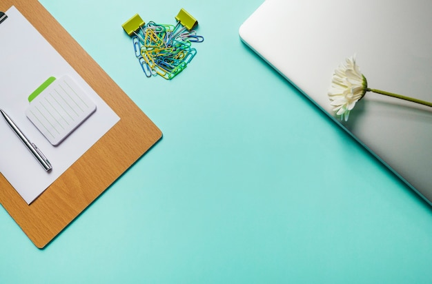 Notepad; pen; paper on clipboard with paperclips and laptop on green background