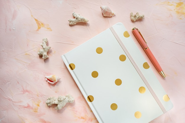 Notepad, pen, sea shells and corals on desk workspace, pink wall. flat lay, top view. sea vacation and summer holidays planning concept