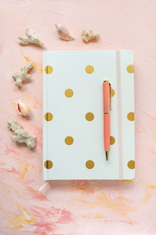 Notepad, pen, sea shells and corals on workspace