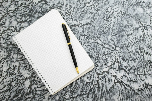 Notepad and pen on a textured gray background