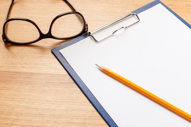 Notepad, pencil and glasses on the wooden background