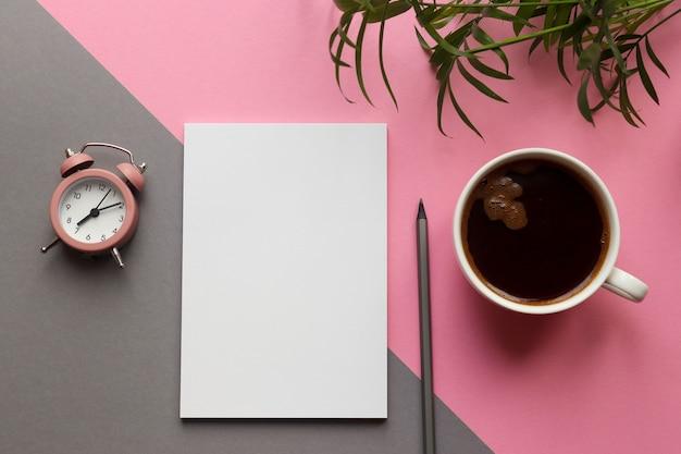 ピンクとグレーの机の上のメモ帳、鉛筆、植物、一杯のコーヒーと目覚まし時計