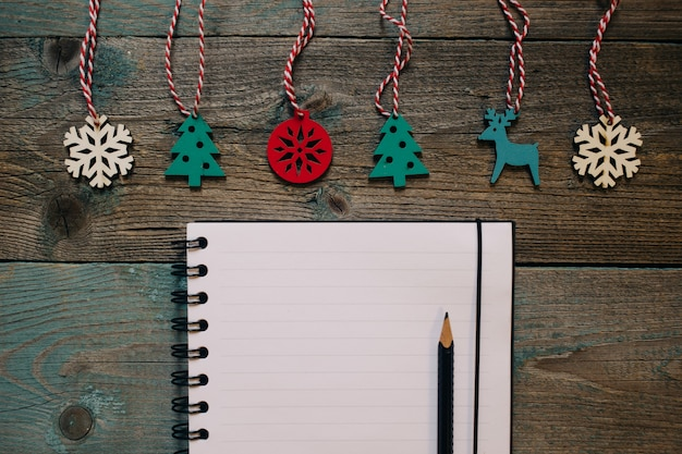 Notepad and pencil, wooden christmas decor, new year, dark wooden flat lay frame.