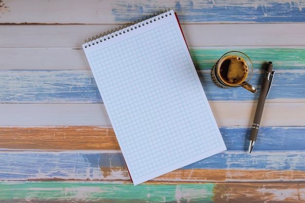 Notepad and pens with coffee on the table.