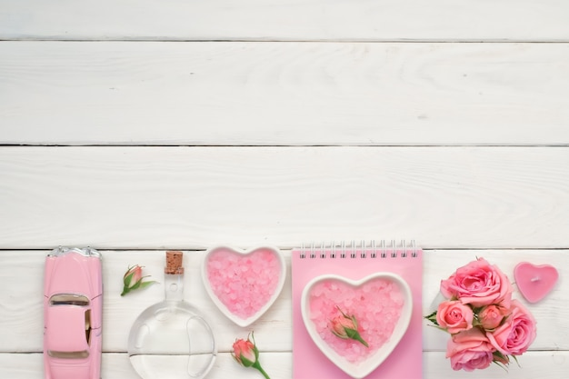 A notepad and pink roses on a white wooden table with space for text bath salts and perfumes empty space flatt was lying down top view