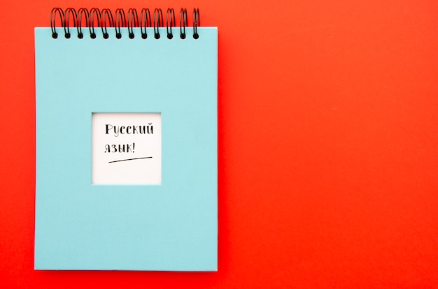 Notepad on red background with copy space