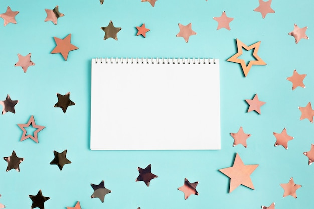 Notepad and stars decoration on blue
