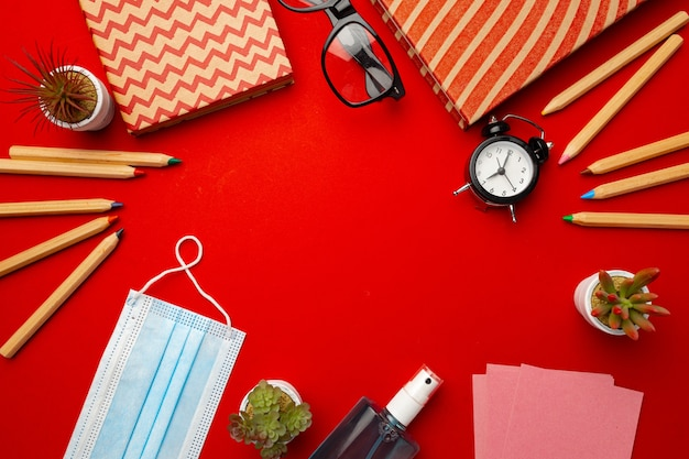Notepad, stationery and mask on red background