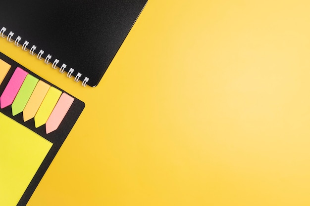 Notepad and sticker on a yellow background.