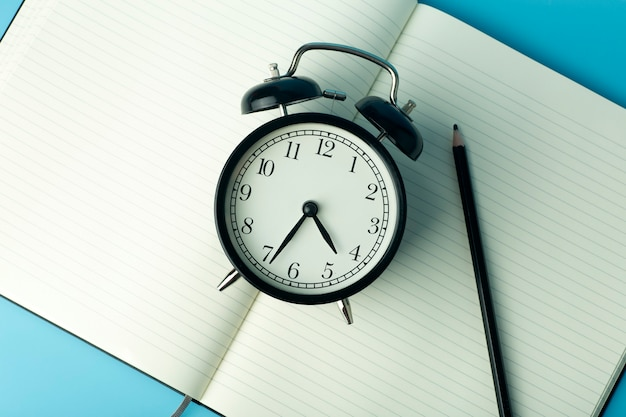 Notepad for sticky notes on desktop with alarm clock. office desktop, management and timing concept.