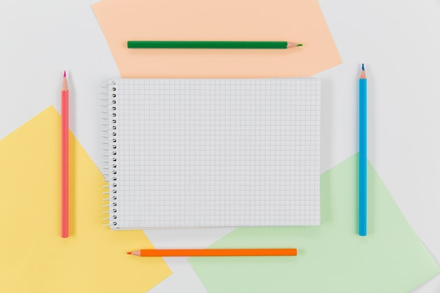Notepad surrounded by colourful pencils