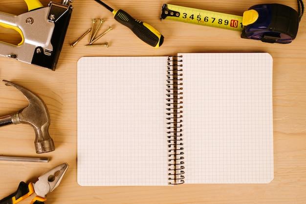 古い木製の背景にほこりっぽいツールに囲まれたメモ帳。職場のペンチ、巻尺、ドライバー、ハンマー、建設用ホッチキス。