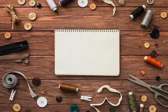 Notepad surrounded by sewing accessories on wooden background