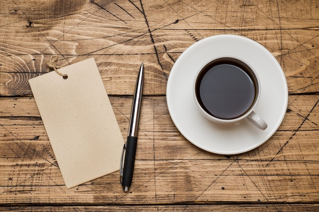 Notepad for text and cup of coffee  wooden background.