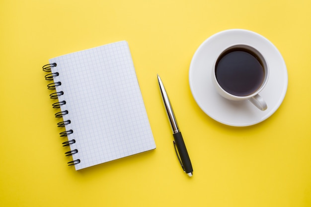 Notepad for text and cup of coffee yellow table with copy space. education and office concept