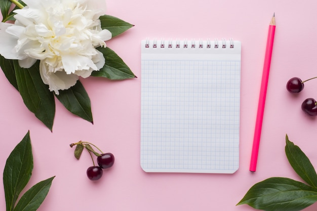 Notepad for text white flowers peony cherry berries on pastel pink surface