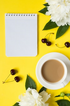 Notepad for text white peony flowers cherry berries cup of coffee on yellow bright background.